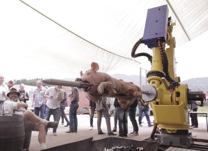 Als Highlight der HMS-Mechatronik-Veranstaltung wurde ein 35 kg schweres Ferkel von einem FANUC Industrieroboter M-900iA/350 gegrillt.