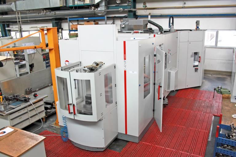 5-Achsen-CNC-Hochleistungs-Bearbeitungszentrum C 42 U mit dem frontseitig angedockten Palettenwechsler PW 850 und dem im Vordergrund befindlichen Rüstplatz in der mechanischen Fertigung bei Reis Robotics in Obernburg.