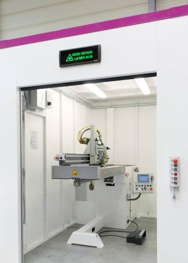Die Längsnahtlaserschweißmaschine ELENA-Laser in ihrer Umhausung mit Schnelllauftor. Die Maschine schweißt nur bei geschlossenem Tor. Ist der Schweißvorgang beendet, öffnet sich das Tor automatisch. (Bild: Schnelldorfer Maschinenbau)