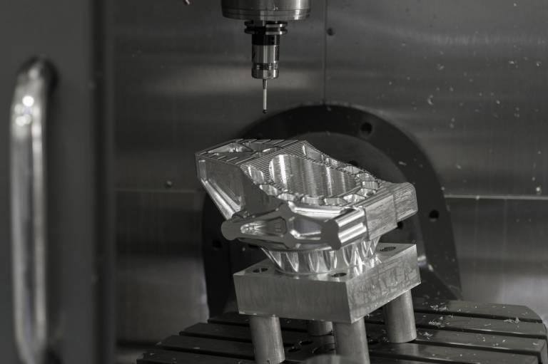 Dieses komplexe, aus Magnesium bestehende Werkstück wird auf der UMC-750 gefertigt. Zahlreiche Konturen, wie Bogen, Rippen, Vorsprünge, unregelmäßig geformte Taschen und Schrägen werden eingearbeitet, die teilweise bis auf 0,02 mm genau sein müssen.