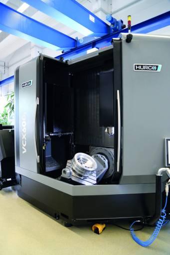 Das neue 5-Achs-Bearbeitungszentrum VCX 600i von Hurco: Die 45°-Tür ermöglicht ergonomisches Arbeiten am Maschinentisch ohne Störkante durch Gegenlager. Mit den Türen wird auch die Kabinendecke geöffnet und die Kranbeladung ermöglicht.