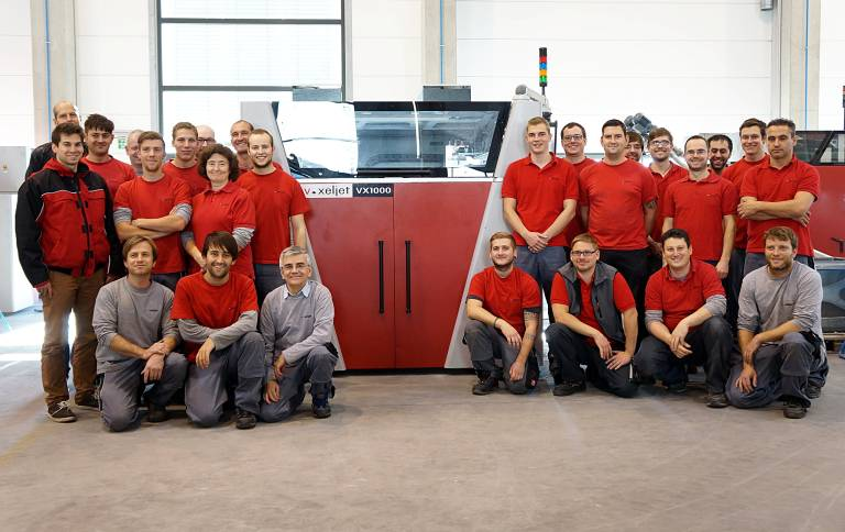 Das Team von voxeljet freut sich über das 100ste installierte 3D-Drucksystem: eine VX1000.
