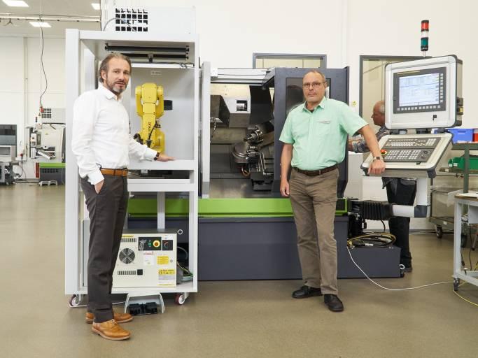 Bedienerlos produktiv: Rainer Jehle (l.), Geschäftsführer der Carl Benzinger GmbH in Pforzheim, und Dieter Wentz, Vertriebsleiter, präsentieren das Präzisionsdrehzentrum GoFuture BX mit der kompakten, flexibel an mehreren Maschinen im Wechsel einsetzbaren Roboterzelle.
