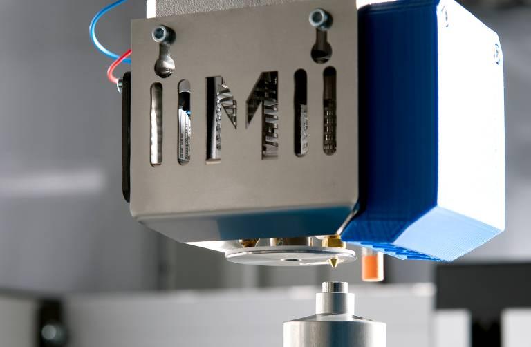 Der Vierfachdruckkopf Multec4Move mit patentiertem Düsenverschluss ist das Herzstück der Maschinen von Multec. Eine integrierte Abstandsmessung (oranger Sensor) ermöglicht eine automatische Bettnivellierung. (Bilder: Brigitte Müller)
