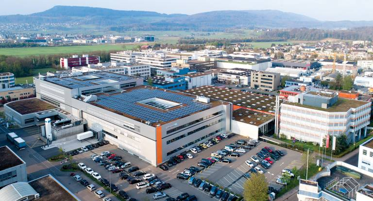 Der 2017 fertiggestellte Neubau in Reinach (Schweiz) bietet weitere 25.000 Quadratmeter Nutzfläche für Büros und Produktion. Die auf dem Dach installierte Solaranlage liefert bis zu 500.000 Kilowattstunden Strom im Jahr.