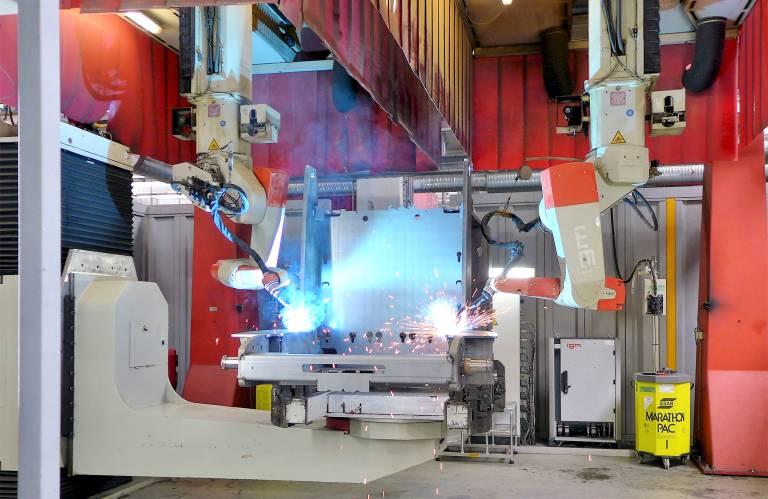 In einer igm-Schweißzelle in Degernpoint schweißen zwei igm-Roboter gleichzeitig einen Fahrzeugrahmen. Damit stets in der qualitätssichernden Wannenlage geschweißt wird, ist der igm-Manipulator bei diesem Großteil zusätzlich mit einem Höhenfahrwerk ausgerüstet.