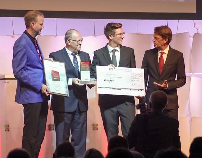 """Alexander Atzberger freut sich über den Gewinn des EWM-Awards """"Physics of Welding"""" (v. l. n. r.): Prof. Dr. Michael Rethmeier (Bundesanstalt für Materialforschung und –prüfung (BAM)), Robert Stöckl (Vorstand Vertrieb der EWM AG), Gewinner Alexander Atzberger und Moderator Rudi Cerne."""