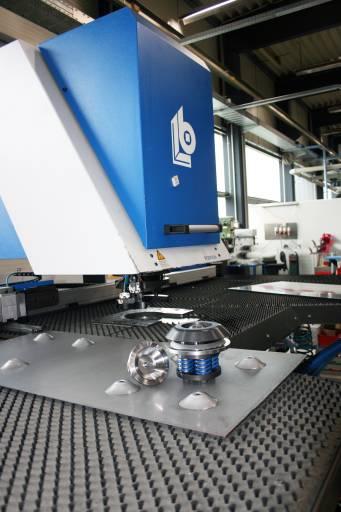Produktion von Verschlussdeckeln aus Stahlblech für Wassertechnik-, Filter- und Fördersysteme: Hohe Präge-/Umformbearbeitung durch ein Sonderwerkzeug mit großem Federpakt im Unterteil für hohe Abstreifkräfte. Der erhöhte Bauraum erlaubt Präge-/Umformhöhen in vielen Dimensionen.