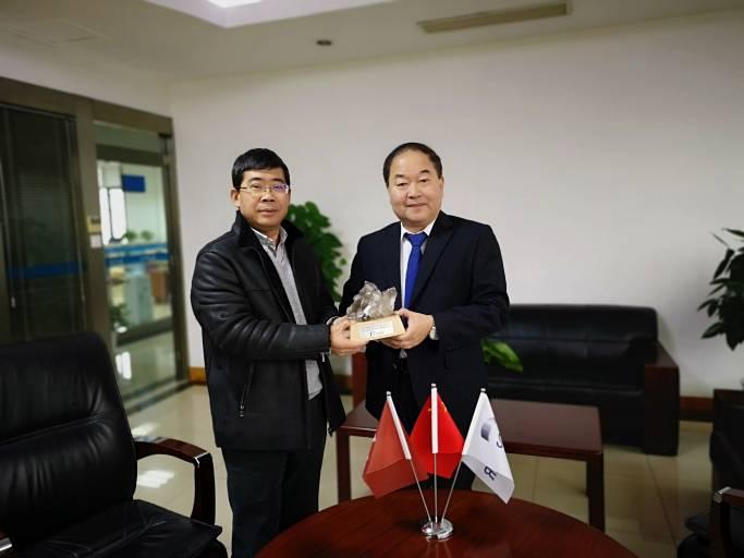 Zhao Jianwei, Senior Sales Manager für Studer Maschinen bei Unuted Grinding China (rechts), übergibt den Schweizer Bergkristall an Yongjun Wang, Deputy General Manager bei Wuhan Hangda Aero Science & Technology Development Co., Ltd (links).