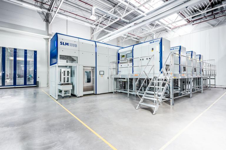 Die Multi-Maschinen-Konfiguration kann aus bis zu fünf baugleichen Maschinen (hier vier SLM®800), der automatischen Auspackstation SLM®HUB, dem Bauzylindermagazin (BCM) und der zentralen Pulverstation (CPS) mit einem tragbaren Behälter bestehen.