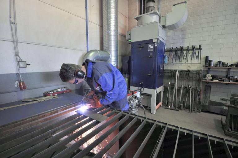 Mitarbeiter Lars Föcking bei der Arbeit am Handplasmaschneidtisch. Partikel werden durch die Untertischabsaugung direkt abgeschieden. Ein Funkenvorabscheider sorgt für zusätzliche Sicherheit.