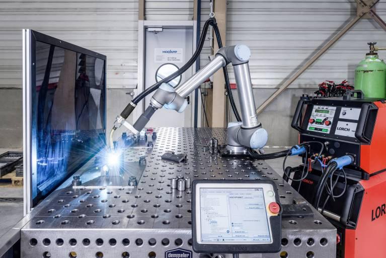 Vorteil der großen Armlänge des UR 10: Während der Cobot an einer Vorrichtung schweißt, kann an einer zweiten Vorrichtung auf dem Arbeitstisch bereits das nächste Werkstück eingelegt werden.