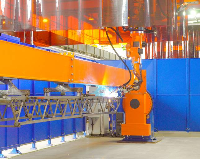 Zwei baugleiche Roboteranlagen von Cloos schweißen  Drehleiterelemente für Feuerwehrhubfahrzeuge. Eine weitere kompakte Roboteranlage schweißt Elemente für Korbmastträger und verschiedene Kleinteile.