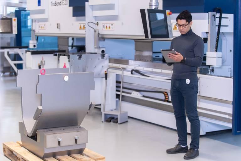 """Ein Mitarbeiter ortet mithilfe von """"omlox"""" ein Werkstück auf einer Palette. Der einheitliche Standard ermöglicht es, Ortungstechnologien und -produkte verschiedener Hersteller zu kombinieren."""