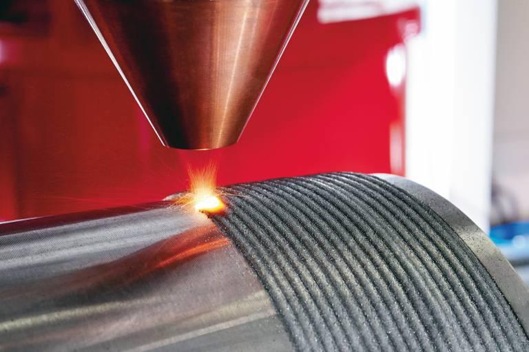 Beim Laser Metal Deposition (LMD-P) wird das Metallpulver ringförmig mithilfe von Prozessgas als Träger- und Schutzgas in den Laserstrahl gesprüht und von diesem geschmolzen. Verglichen mit dem Pulverbettverfahren ist es schneller und kostengünstiger, aber weniger präzise.
