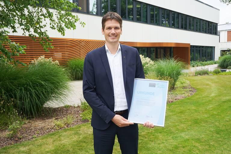 Dr. Stephan Middelkamp, Zentralbereichsleiter Qualität und Technologien bei der Harting Technologiegruppe, präsentiert stolz die Bescheinigung der zehnjährigen Mitgliedschaft beim Verband Klimaschutz-Unternehmen e. V.